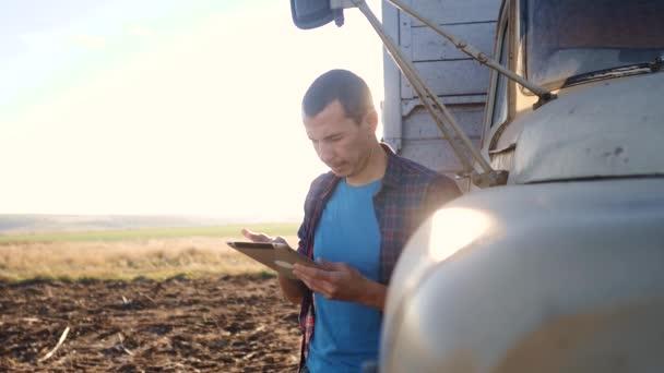 Smart Farming. Der Fahrer steht mit einem digitalen Tablet in der Nähe des Lastwagens. Zeitlupenvideo. Porträt Geschäftsmann Bauer steht in Lebensstil das Feld Erntezeit Auto. Landwirt fährt mit einem