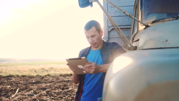 smart farming. man farmer driver stands with a digital tablet near the truck. slow motion lifestyle video. Portrait businessman farmer standing in the field harvesting season car. Farmer driver uses a