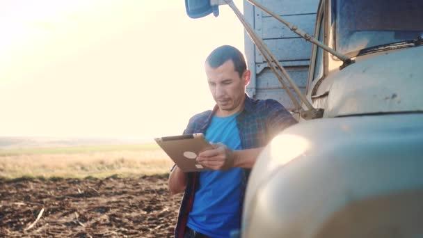 Smart Farming. Der Fahrer steht mit einem digitalen Tablet in der Nähe des Lastwagens. Zeitlupenvideo. Porträt Geschäftsmann Bauer steht auf dem Feld Erntewagen. Landwirt fährt mit Tablet