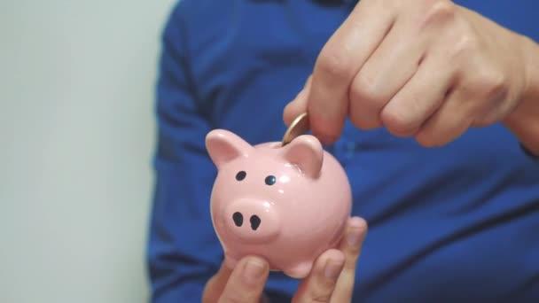 Zwei Geschäftsleute legen in Teamarbeit Ersparnisse in ein Sparschwein. Zwei Männer Sparschwein Geschäftskonzept. Zeitlupenvideo. Geld zu sparen ist eine Investition in die Zukunft. Bankeninvestitionen und Finanzwesen