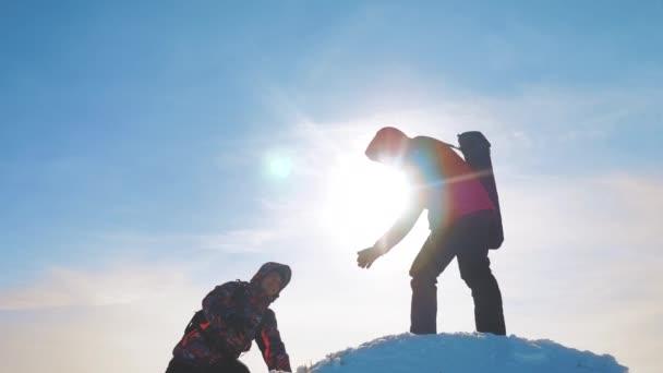 Týmová práce. dva cyklisty turisty nabízí pomocnou ruku. Zimní výhra úspěch dosáhla vrcholu hory. Turisté horolezců vylézt na vrchol horské týmová práce obchodní cesty silueta koncepce