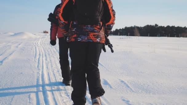 Týmová práce. muži turisté fotografů jít na sněhu v zimě se stativem lezení, chůzi nejvyšší hory skály vrchol skupiny týmu slunečního světla. nohy projít výlet sněhu zimní sníh. zpomalené video