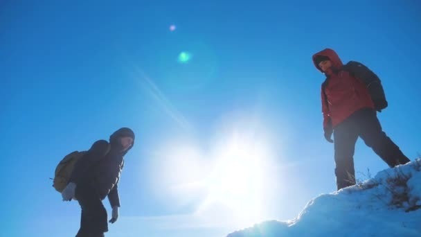 teamwork tourists business travel trip lends a helping hand. two men with backpacks hiking help each winter snow other silhouette in mountains with sunlight. slow motion video. rock climbers teamwork