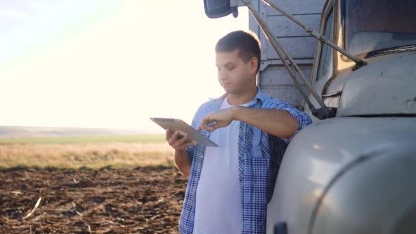 Smart Farming. Der Fahrer steht mit einem digitalen Tablet in der Nähe des Lastwagens. Zeitlupenvideo. Porträt Geschäftsmann Bauer steht auf dem Feld Erntewagen. Landwirt setzt Fahrer ein