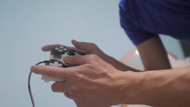 az ember fogalma játékpad kéz videó konzol a TV-ben. Gamer játszani játékvezérlő vezérlő. Kézi ragaszkodik új botkormány játék video vigasztal-ra TV. Gaming életmód ember gazdaság szimulátor joypad