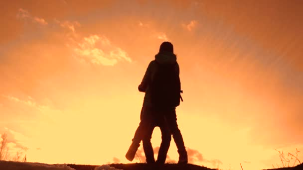 father and daughter teamwork happy family tourists silhouette concept holding hands spinning funny video. team dad and daughter on sunset play dabble the top of the mountain with backpacks. winning