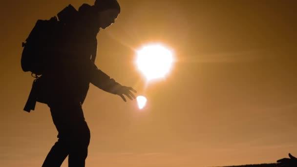 Týmová práce turistů obchodní cesty cesty podává pomocnou ruku. dva muži s batohy turistické pomoci každý silueta v horách s slunečního světla. zpomalené video. Týmová práce přátelství turistické Nápověda