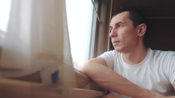 muž jízdy vlaku železniční vyhlíží životní styl okna. cestovatel koncepce vlaku železniční cesta cestování. zpomalené video. krásné z okna pohybující vlak železniční cesty Rusko zimní