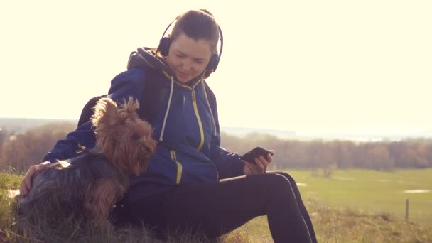 middle-aged woman and dog Yorkshire Terrier tourist with a backpack in the headphones listens to music looks into the smartphone with a dog in nature rests lifestyle . Beautiful woman and dog