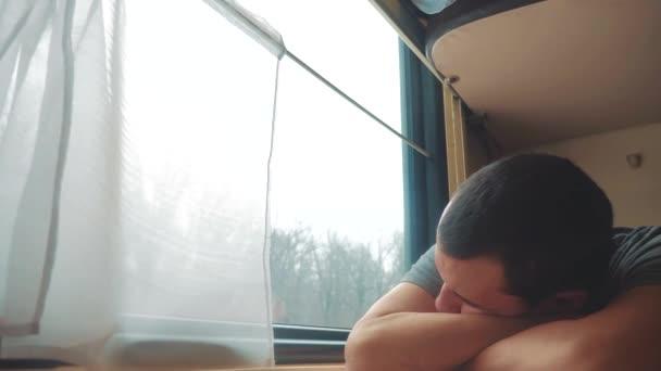 man sleeps in train tired long journey by rail. train railroad journey travel. slow motion video. beautiful from window of a moving train railway trip Russia winter. man is sleeping lifestyle railroad