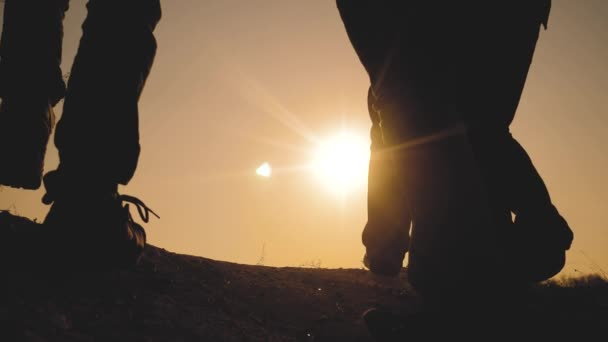 teamwork business travel concept. legs silhouette group hikers of people walking on the top of the mountain with backpacks sunset sun light. slow motion video. campaign tourists with lifestyle