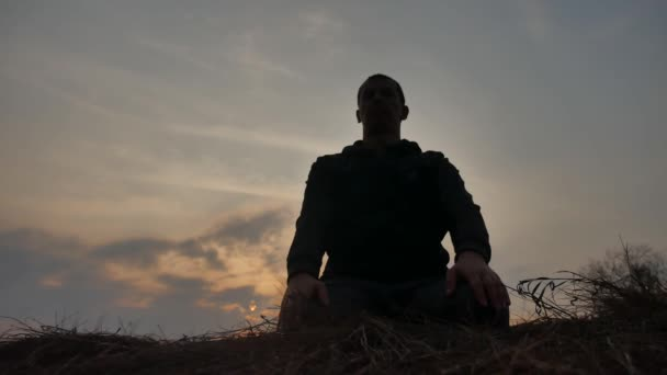 religion concept. silhouette of a male monk engaged in meditation lifestyle at sunset sunlight. Buddhist prayer at sunset healthy way of life nature