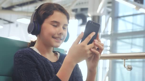 airport waiting hall room for a flight by plane. young happy teen girl in headphones listening to the music on smartphone chatting communicates in the messenger. lifestyle teenager girl in social
