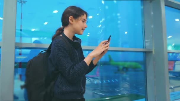 daughter traveler with a backpack airplane flights airport concept. girl teenager with a smartphone looks out the window at the airport area airplanes and bus at a distance. teen girl looks at the