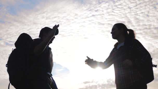 teamwork man and woman business journey concept win. team tourists man and woman sunset silhouette help shake hands success victory. slow motion video. tourism husband and wife on top of the mountain