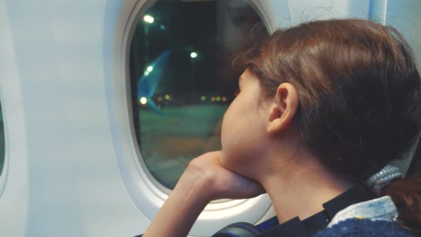 teen girl aviation aircraft concept. young girl looks out the airplane sitting by the window. flight at night by plane lifestyle