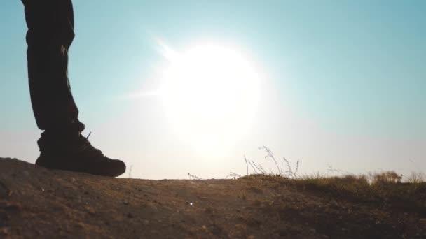 pojetí cestovního ruchu v zaměstnání. nožky siluety lidí, kteří chodí po vrcholku hory s batohy na slunci. video s pomalým pohybem. kampaně pro turisty s batohy