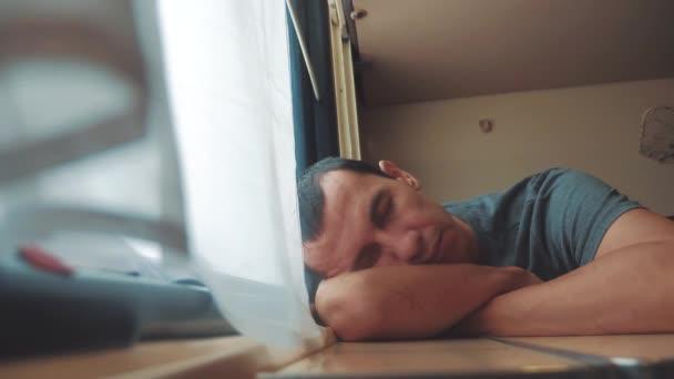 man sleeps in train tired long journey by rail. train railroad journey travel. slow motion video. beautiful from lifestyle window of a moving train railway trip Russia winter. man is sleeping railroad