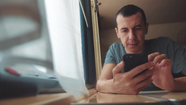 man sleeps in train tired long journey by rail. train railroad journey travel lifestyle . slow motion video. beautiful from window of a moving train railway trip Russia winter. man is sleeping