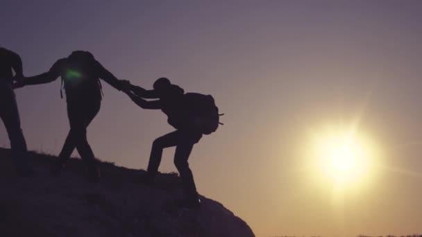 Teamwork hilft Business Lifestyle Reise Silhouette Konzept. Gruppe von Touristen hilft beim Besteigen der Felswände. Bergsteiger erklimmen Gipfel und überwinden Strapazen auf dem Weg zum Sieg