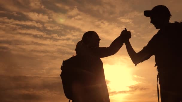 teamwork business lifestyle journey concept win. team tourists man and woman sunset silhouette help shake hands success victory. slow motion video. tourism husband and wife on top of the mountain have