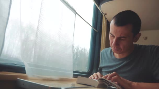 man reading a book in a train long journey. railroad travel concept coach train journey. view beautiful from the window of a moving train railway lifestyle Russia winter. interior inside train