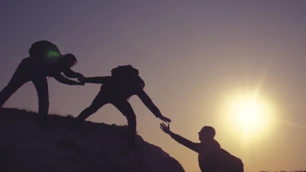 Teamarbeit hilft bei der Gestaltung des Lifestyles für Geschäftsreisen. Gruppe von Touristen hilft beim Besteigen der Felswände. Bergsteiger erklimmen den Gipfel und überwinden Strapazen