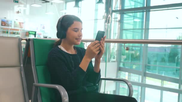airport waiting hall room for a flight by plane. young happy teenage girl in headphones listening to the music on smartphone chatting communicates in the messenger. teenager girl in social networks