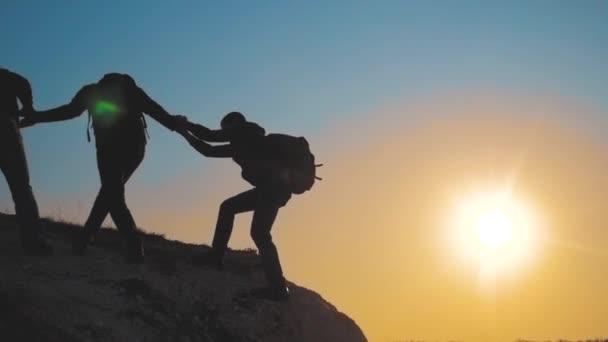 Teamarbeit hilft bei Geschäftsreisen Silhouette Lifestyle-Konzept. Gruppe von Touristen hilft beim Besteigen der Felswände. Bergsteiger erklimmen Gipfel und überwinden Strapazen auf dem Weg zum Sieg