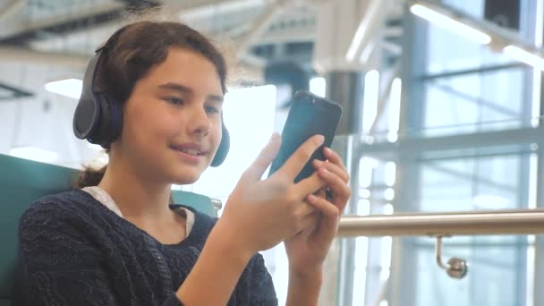 airport waiting hall room for a flight by plane. young happy teen girl in headphones listening to the music on smartphone lifestyle chatting communicates in the messenger. teenager girl in social