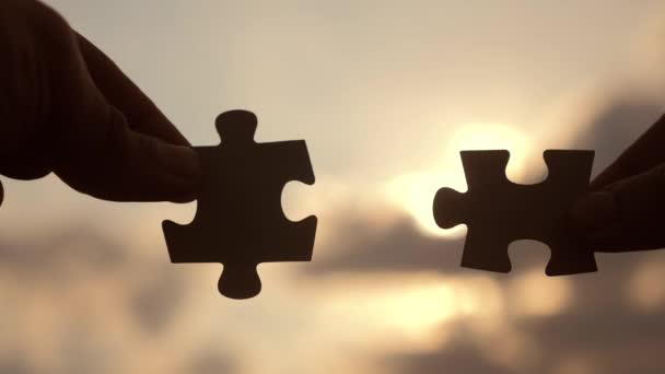 koncepce podnikových financí. mužské ruce spojují dvě hádanky proti siluetě západu slunce. symbol týmovo asociace a propojení životního stylu. strategie podnikání