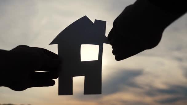 šťastný koncept výstavby rodinných domů. Muž, který drží doma papírový domek ve svých rukou při slunečním svitu siluetě. Ekologie život video symbol životní styl