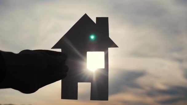 happy family house construction concept. lifestyle man holding home a paper house in his hands at sunset silhouette sunlight. ecology life video symbol