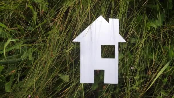šťastný koncept rodinného stavebního domu. v zelené trávě v přírodě stánky s papírovým domem. život symbol ekologie video životní styl
