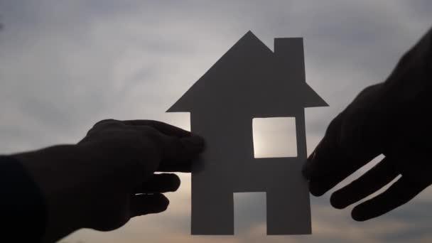 šťastný koncept výstavby rodinných domů. Muž, který drží doma papírový domek v dlaních za slunečních paprsků ve stylu západu slunce. životní ekologie symbol videa