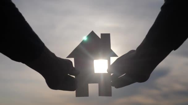 glücklich Familie Bau Haus Lifestyle-Konzept. Mann mit einem Papierhäuschen in der Hand im Sonnenuntergang. lebensökologisches Videosymbol