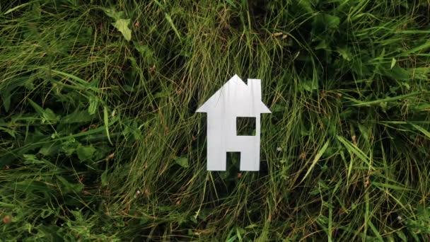 boldog család építőipari ház életmód koncepció. papírház áll a zöld fű a természetben. élet szimbóluma ökológia videó