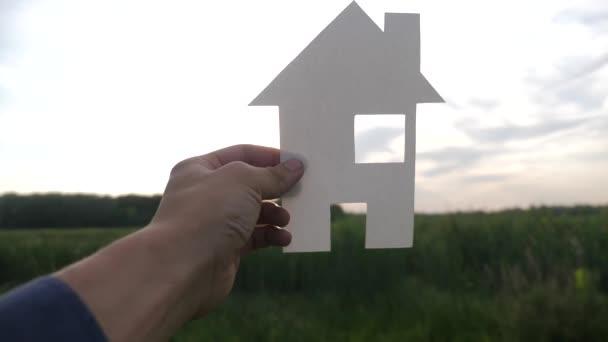 šťastný koncept rodinného stavebního domu. Muž, který drží doma papírový domek ve svém životním stylu a má ruce za slunečních paprsků. životní symbol ekologie video