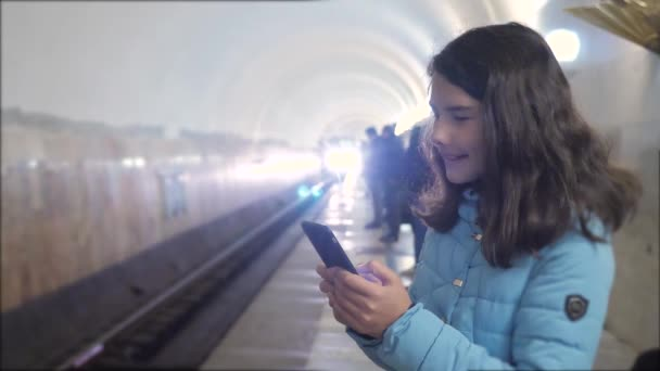 girl teenager in the underground subway rides in the subway waiting for the arrival of train, holds smartphone. little girl brunette daughter search the internet on the web social lifestyle networks