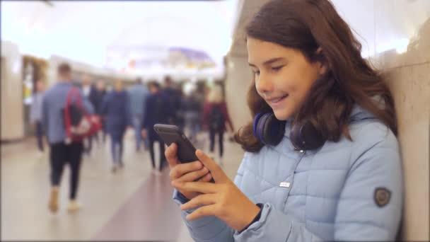 dospívající dívka s smartphone a sluchátky čekající na metro spousta lidí se v podzemí překřížit. koncepce ilegálního lidu metra. mladá dívka Bruneta dcera prohledá Internet na webu