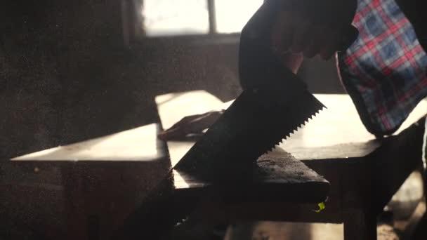 Schreiner handgemachtes und handwerkliches Konzept Zeitlupe Video. Tischler sägt in einer Werkstatt einen Baum und sägt Sonnenlicht aus einer Fenstersilhouette. Holzarbeiter in Handarbeit bei der Holzverarbeitung beschäftigt