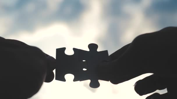teamwork lifestyle business finance concept. male hands connect two puzzles silhouette against the sunset. teamwork symbol of association and connection. business strategy