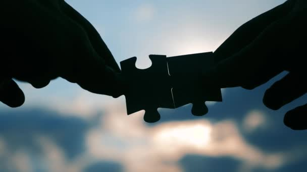 teamwork business finance concept. male hands connect two puzzles silhouette lifestyle against the sunset. symbol teamwork of association and connection. strategy business