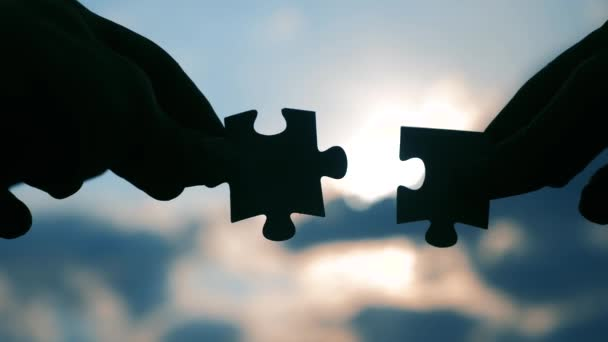 teamwork business finance concept. male hands connect lifestyle two puzzles silhouette against the sunset. symbol teamwork of association and connection. strategy business