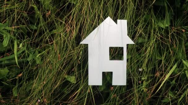 šťastný rodinný stavební život. v zelené trávě v přírodě stánky s papírovým domem. symbol životní ekologie video