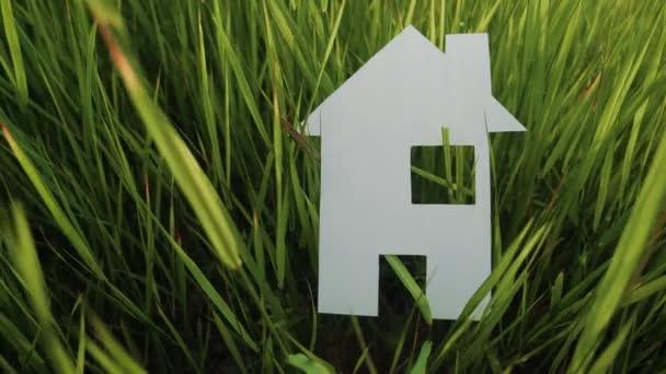 épület boldog családi építőház koncepció. papír ház áll életmód a zöld fű a természetben. szimbólum élet ökológia videó