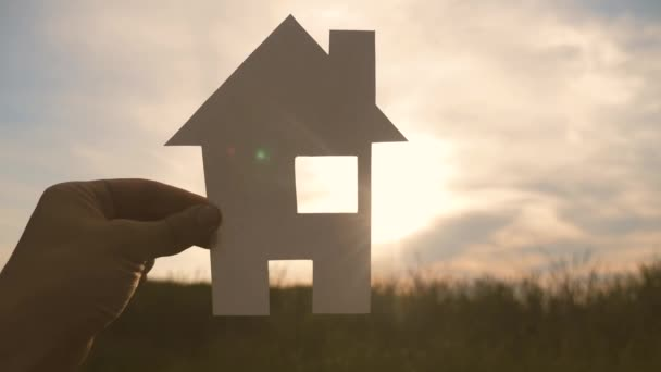 happy family lifestyle construction house concept. man holding home a paper house in his hands at sunset silhouette sunlight. life symbol ecology video