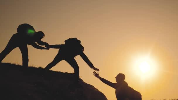 Teamarbeit hilft bei der Gestaltung von Geschäftsreisen. Lifestyle-Gruppe von Touristen hilft beim Besteigen der Felswände. Bergsteiger erklimmen Gipfel und überwinden Strapazen auf dem Weg zum Sieg