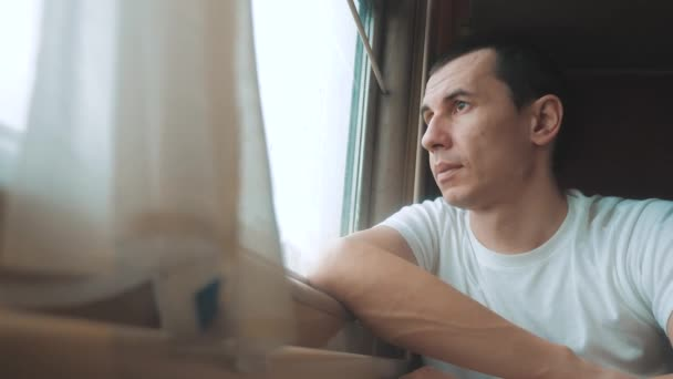 man rides train railway looks out the window. traveler concept train lifestyle railroad journey travel. slow motion video. beautiful from window of a moving train railway trip Russia winter