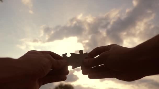 koncepce podnikových financí. mužské ruce spojují dvě hádanky s siluetou proti západu slunce. symbol týmové práce přidružení a připojení. životní styl obchodní strategie